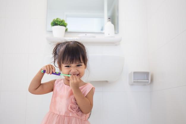 Weinig leuk babymeisje die haar tanden met tandenborstel in de badkamers schoonmaken