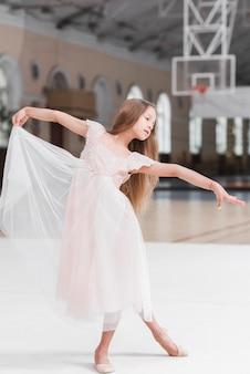 Weinig leuk ballerinameisje die op vloer dansen