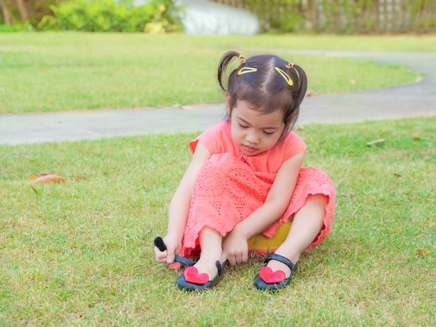 Weinig leuk meisje 3 jaar oud met oranje kleding die haar schoenen probeert aan te zetten.