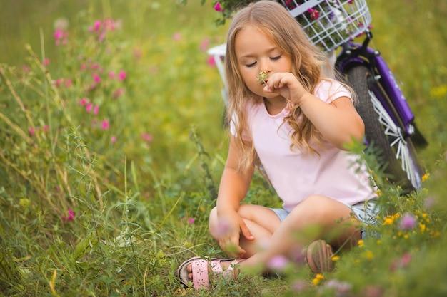 Weinig leuk meisje dat een fiets met mandhoogtepunt van bloemen berijdt. vrolijk kind