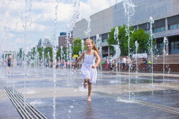 Weinig leuk meisje dat in open straatfontein bij hete zonnige dag loopt