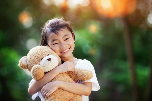 Weinig leuk meisje dat zich in het gras bevindt dat grote teddybeer houdt