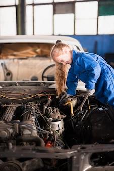 Weinig leuk meisje die auto met moersleutel herstellen