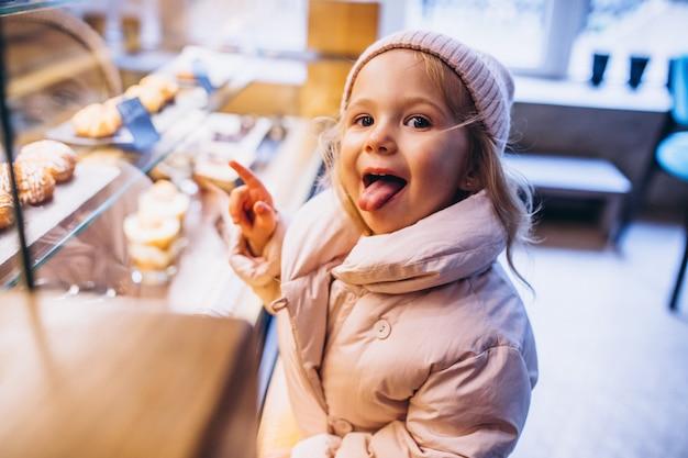 Weinig leuk meisje die dessert in een bakkerij kiezen