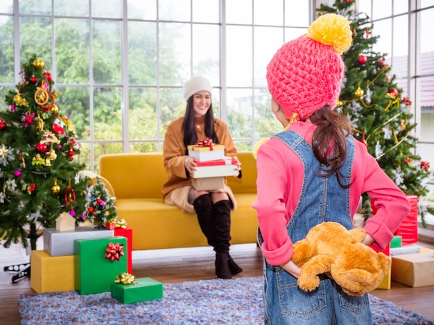 Weinig leuk meisje die een teddybeergift geven aan haar moeder in kerstmisdag. kerstvieringsconcept.