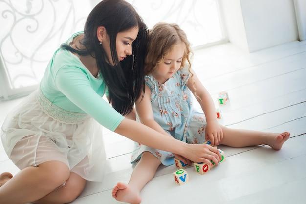 Weinig leuk meisje en haar moeder die en met abc kubussen spelen binnen opleiden. jonge mooie moeder en haar dochter speelblokken.