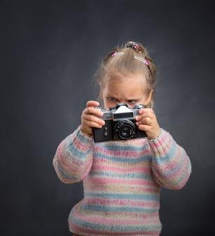 Weinig leuk meisje kijkt foto's naar de camera