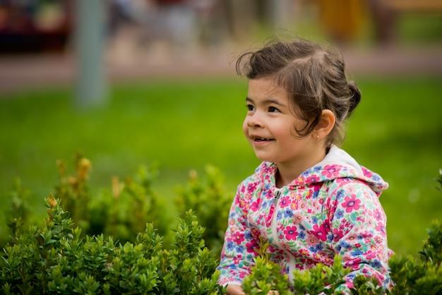 Weinig leuke meisjeszitting in groene struik in en park dat weg glimlacht kijkt