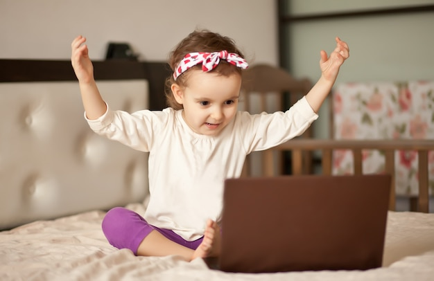 Weinig leuke meisjeszitting op het bed en het gebruiken van een digitaal tabletlaptop notitieboekje. bel vrienden of ouders online.