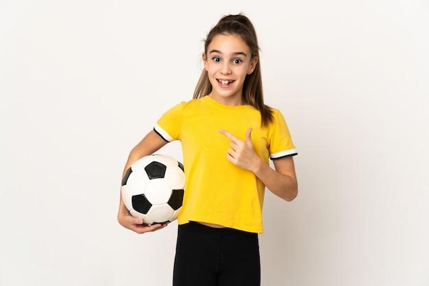 Weinig meisje van de voetballer dat op witte muur met verrassingsgelaatsuitdrukking wordt geïsoleerd