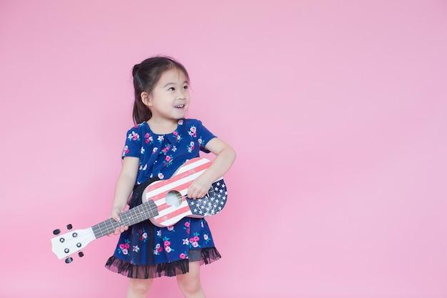 Weinig mooi aziatisch meisje gitaarspelen op roze met kopie ruimte