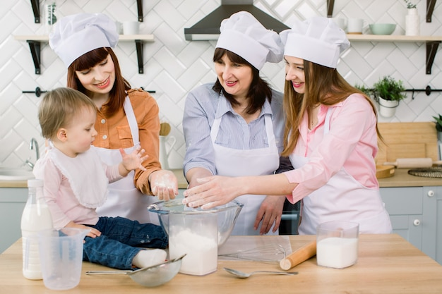 Weinig mooi babymeisje met moeder, tante en grootmoeder die bloem in hun handen houden en samen thuis deeg maken. infant chef bakken concept.