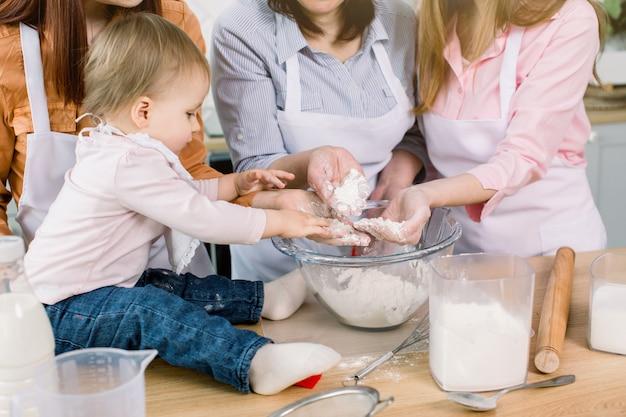 Weinig mooi babymeisje met moeder, tante en grootmoeder die bloem in hun handen houden en samen thuis deeg maken