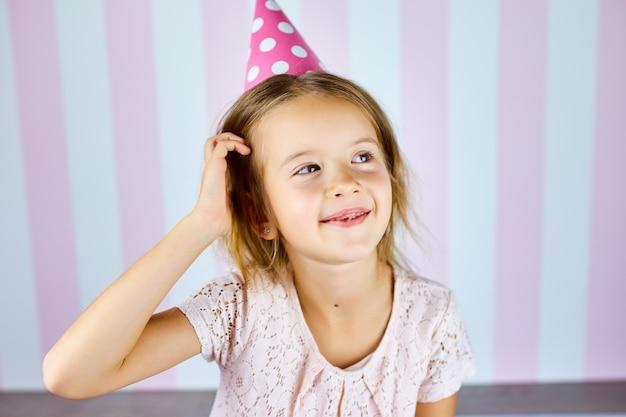 Weinig mooi meisje dat verjaardags roze glb op roze witte streepmuur draagt die met gelukkig gezicht glimlacht. fijne verjaardag.