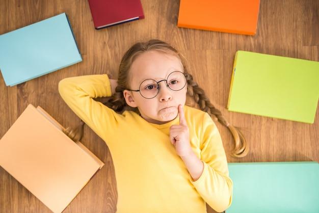 Weinig mooi meisje die in glazen op vloer met boeken leggen.