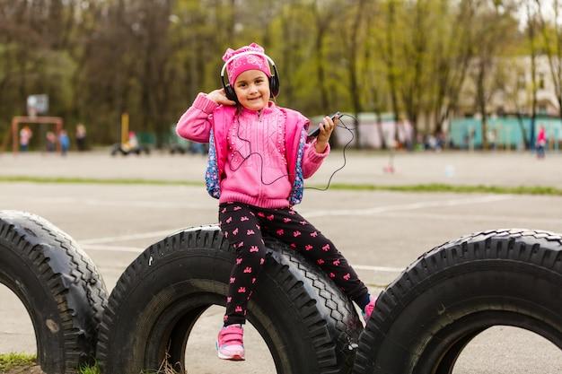 Weinig mooi meisje geniet van de telefoon. ze koptelefoons. kinderen en technologie