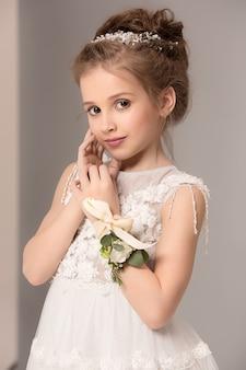 Weinig mooi meisje met bloemen gekleed in trouwjurken