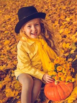 Weinig mooi meisje met blond haar met grote pompoen op de herfstachtergrond. halloween