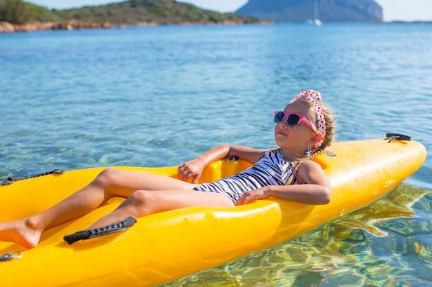 Weinig mooi schattig meisje geniet van kajakken in de heldere blauwe zee