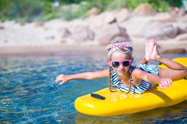 Weinig mooi schattig meisje kajakken in de heldere blauwe zee