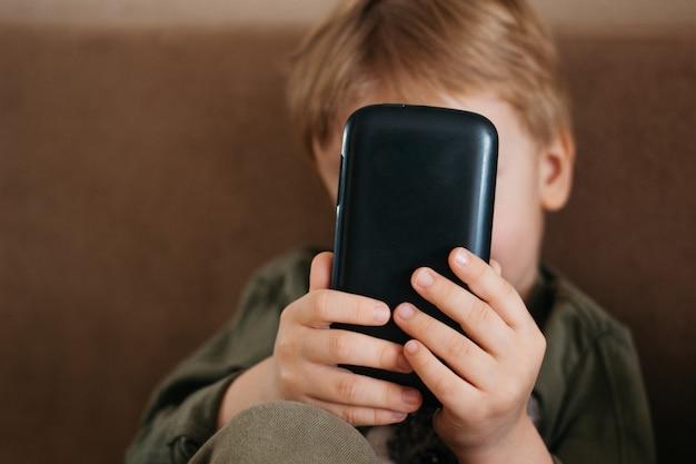 Weinig mooie jongen gebruikt een telefoon, kaukasische smartphone van de jongensgreep.