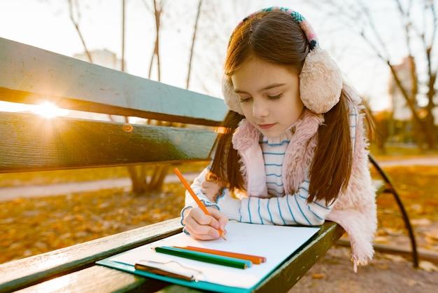 Weinig mooie kunstenaarstekening met kleurpotloden, meisjeszitting op een bank in zonnig de herfstpark