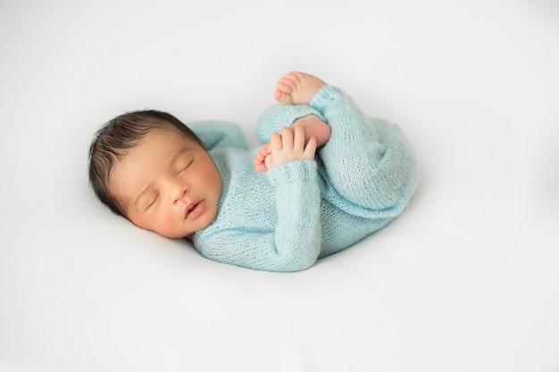 Weinig pasgeboren baby het leggen op weinig witte stoel in blauwe gehaakte pijamas