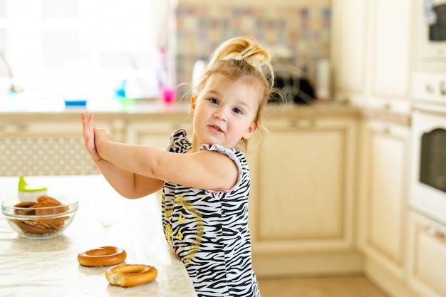 Weinig peuterjong geitje dat lunch in de warme zonnige keuken heeft. blondemeisje met het grappige paardestaart spelen met twee smakelijke ongezuurde broodjes