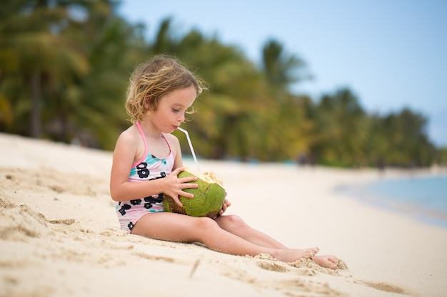 Weinig peuterjong geitjemeisje die kokosnotensap op oceaanstrand drinken.