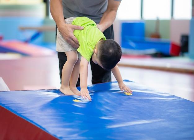 Weinig peuterjongen die bij de binnengymnastiekoefening uitwerkt