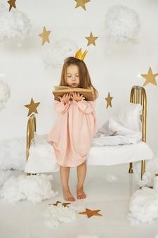Weinig prinses met een toverstaf op een bed in een wolk op een witte achtergrond