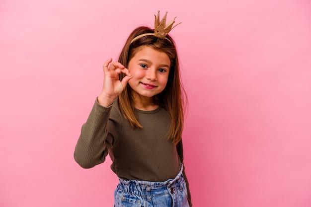 Weinig prinsesmeisje met kroon dat op roze muur wordt geïsoleerd vrolijk en zelfverzekerd tonend ok gebaar