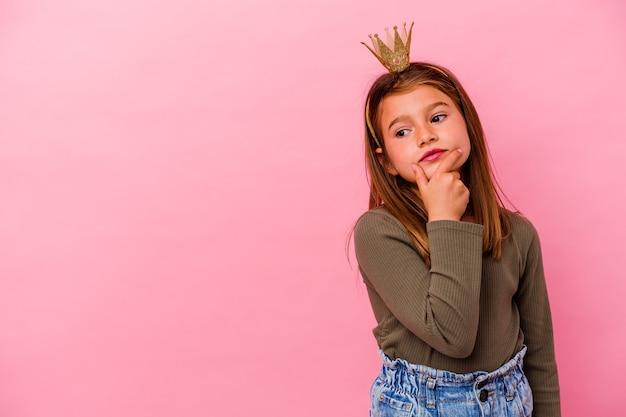 Weinig prinsesmeisje met kroon dat op roze wordt geïsoleerdd zijwaarts kijkt met twijfelachtige en sceptische uitdrukking.