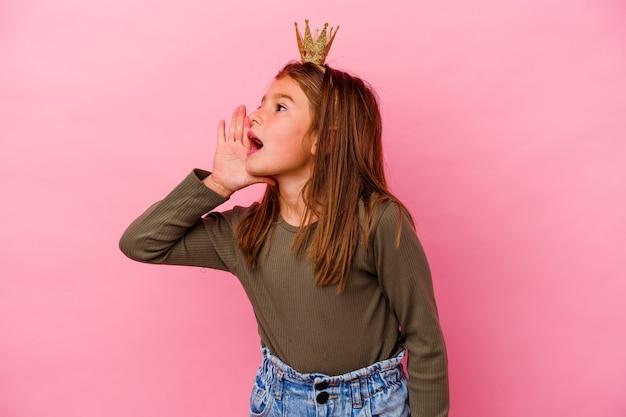 Weinig prinsesmeisje met kroon die op roze muur wordt geïsoleerd die en palm dichtbij geopende mond houdt.