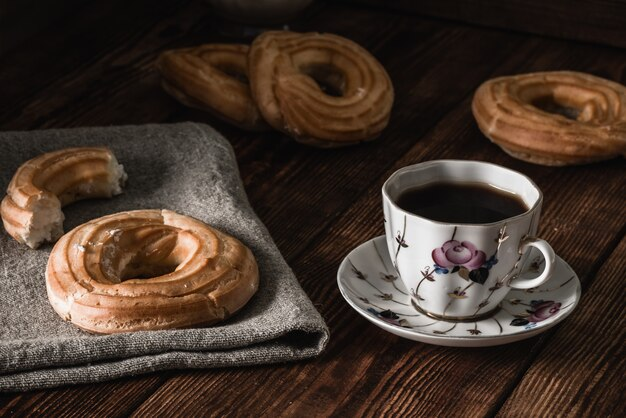 Weinig ronde eclairs met een kopje koffie