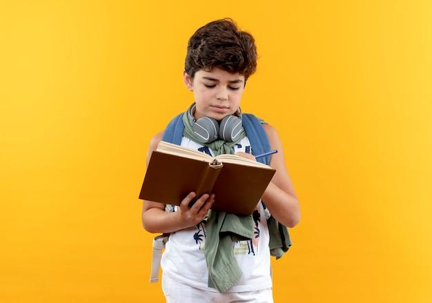 Weinig schooljongen die rugtas en koptelefoon draagt die iets op boek schrijven dat op gele achtergrond wordt geïsoleerd