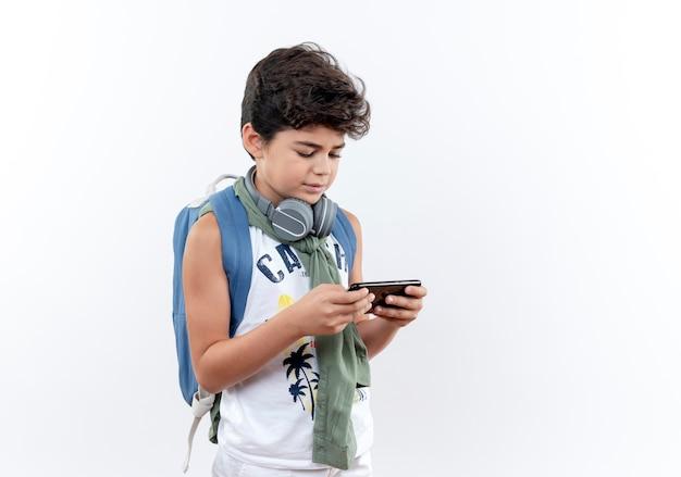 Weinig schooljongen die rugzak en hoofdtelefoons draagt die op telefoon spelen