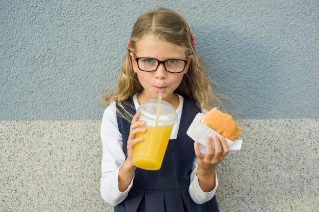 Weinig schoolmeisje die een hamburger en een jus d'orange houden
