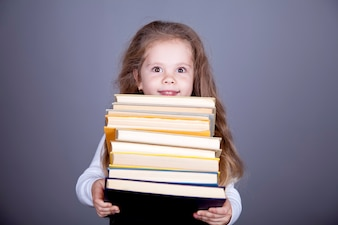 Weinig schoolmeisje met boeken.