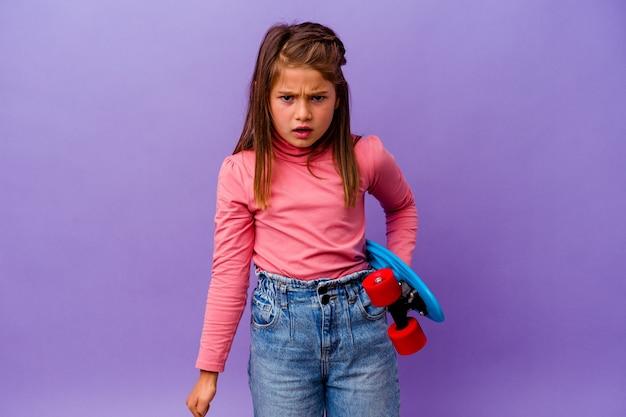 Weinig skater kaukasisch meisje geïsoleerd op blauw schreeuwen erg boos en agressief.