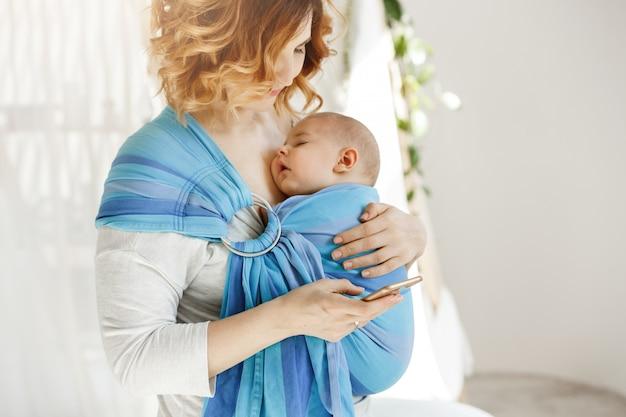 Weinig slaap van de babyjongen strak met open mond en zoete gezichtsuitdrukking in babyslinger terwijl nieuws van de mamma het rustende lezing wereld op telefoon. familie concept.