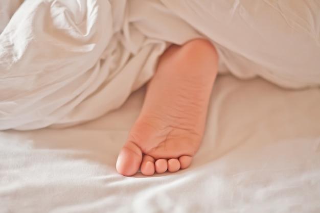 Weinig slaap van het jongensjonge geitje toont voeten onder uit witte deken