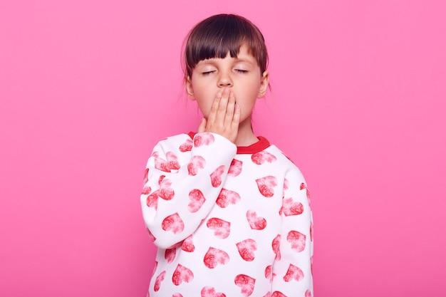 Weinig slaperig vrouwelijk kind dat ogen gesloten houdt, mond bedekt met palm terwijl geeuwt, witte trui met hartjes draagt, geïsoleerd over roze muur.