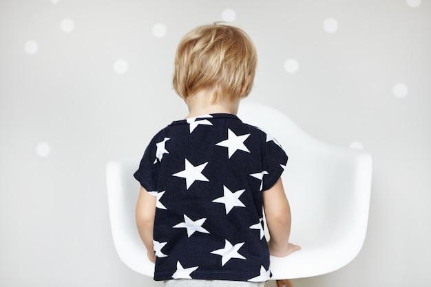 Weinig speelse blanke jongen met blond haar gekleed in een t-shirt met sterren, speelt met zijn speelgoed in de kinderkamer. achteraanzicht van schattige lieve peuter voor witte stoel thuis.