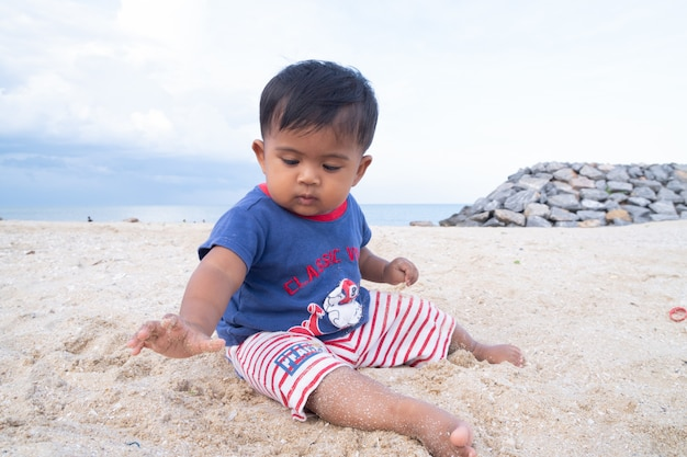 Weinig spel van de babyjongen op het strand
