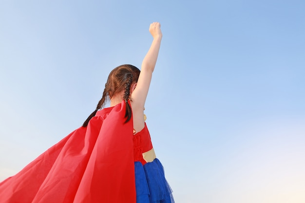 Weinig superhero van het kindmeisje in een gebaar om op duidelijke blauwe hemelachtergrond te vliegen.