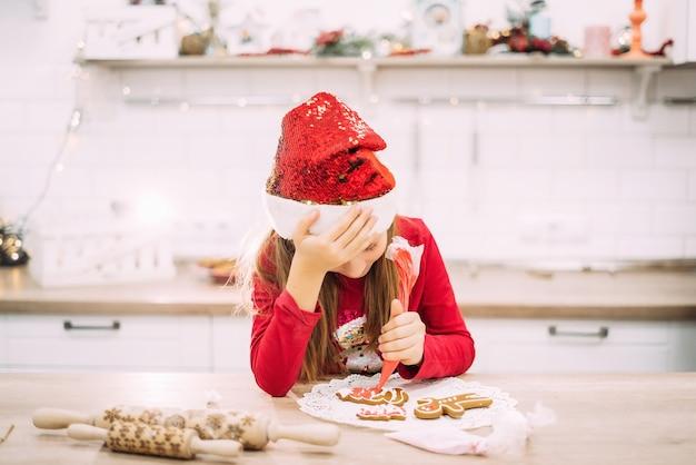 Weinig tienermeisje zit in de keuken en houdt haar hoofd, peperkoekkoekjes met suikerglazuur schilderen