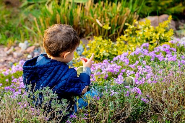 Weinig todler die met bloemen in de tuin speelt