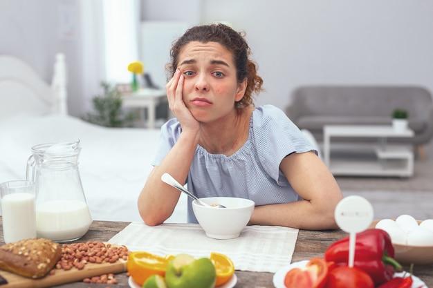 Weinig trek. adolescente dame boven een eettafel die er ongeïnteresseerd uitzag in haar maaltijd en duidelijk een vreselijk gebrek aan eetlust ervaart