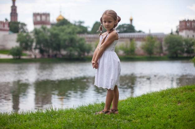 Weinig verlegen meisje dat openlucht dichtbij het meer loopt